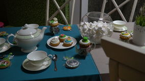 Tea set on a blue and gray tablecloth on the background of wallpaper as a forest. Tea set with desserts and a grass vase on a blue and gray tablecloth on the stock video footage