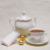 Tea set with box of gold candies Royalty Free Stock Photography