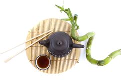 Tea set and a branch of bamboo Royalty Free Stock Photography