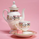 Tea set with candy on pink background Stock Image