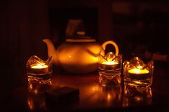 Tea set on a dark background and candle light is a concept of traditional british tea. Drinking Stock Image