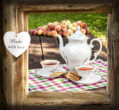 Tea set in garden in wooden frame with heart. Stock Photography