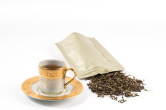 Tea set gold cup and tea bag Royalty Free Stock Photo