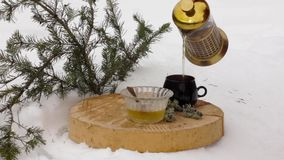 Tea set with honey: pouring hot tea from transparent teapot to black cup on a wooden stand among the snow.  stock footage