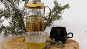 Tea set with honey: pouring hot tea from transparent teapot to black cup on a wooden stand among the snow.  stock video