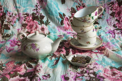 A tea set. Kettle, set different cups, tea with flowers of heather on fabric background with floral pattern Royalty Free Stock Photography