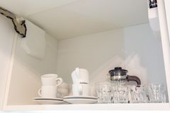 Tea set and kettle on the shelf in the kitchen cupboard royalty free stock photography