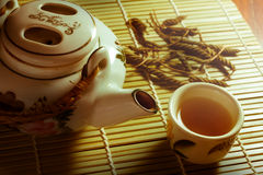 Tea set with leaves on bamboo mat Royalty Free Stock Image