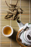 Tea set with leaves on bamboo mat. Stock Photography