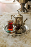 Tea set in oriental style in pear shaped glass with vintage kettle and dates fruit Royalty Free Stock Photo