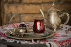 Tea set in oriental style in pear shaped glass with vintage kettle and dates fruit. Tea set in oriental style in pear shaped glass with spoon and vintage kettle Stock Images