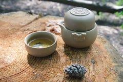 Tea set outdoors on a wooden stump Stock Photo