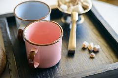 Tea set with two metal cups, sugar tongs and lumps. Close up vintage teaset with blue and pink metal mugs, sugar-tongs and lumps of sugar on wooden tray Stock Images