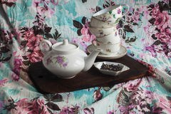 Tea set on a wooden board. Kettle, set different cups, tea with flowers of heather on fabric background with floral pattern Stock Photo