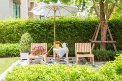 Tea set on wooden table under white umbrella in the garden. Stock Photo