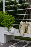 Tea set and yellow pillows on white bench. In garden royalty free stock photography