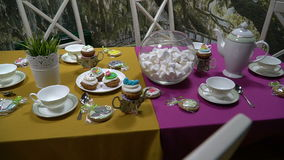 Tea set on a yellow and purple tablecloth on the background of wallpaper as a forest. Tea set with desserts and a herb of grass on a yellow and purple tablecloth stock video