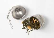 Tea skimmer. With dried green tea leaves and orange husk Royalty Free Stock Photography