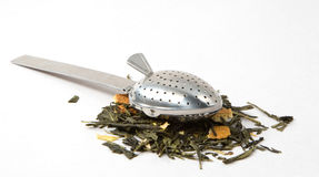 Tea skimmer. With dried green tea leaves and orange husk Royalty Free Stock Image