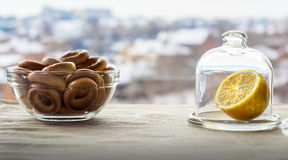 For tea. Snack with tea. Drying in a saucer and a lemon in a glass flask on the table Royalty Free Stock Images