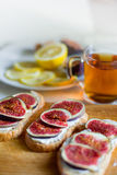 Tea with snaks with figs and cream cheese on white textile background Stock Photo