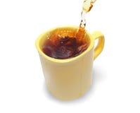 Tea som hälls in i tea, kuper på en vit Arkivfoton