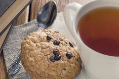 A cup of tea and some chocolate chip cookies over a books on a brown wooden table. A tea and some chocolate chip cookies over a books on a brown wooden table royalty free stock images