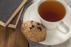 A cup of tea and some chocolate chip cookies over a books on a brown wooden table. A tea and some chocolate chip cookies over a books on a brown wooden table stock photography