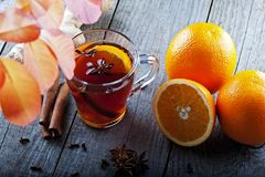 Tea with spices and orange amid autumn leaves Royalty Free Stock Photo