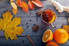 Tea with spices and orange amid autumn leaves Stock Photo