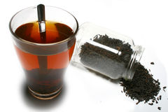 Tea spilled out of jar and a glass of tea Royalty Free Stock Photo