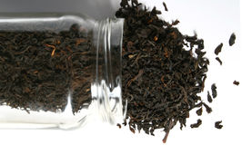 Tea spilling out a glass jar. Black tea spilled out of a glass jar stock photography