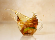 Tea splash in glass cup.Hot lemon drink. Stock Images
