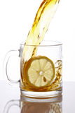 Tea splashing. In a transparent glass mug with a lemon slice, with reflection on a white background stock photos