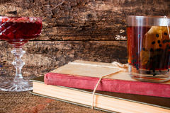 Tea on a stack of books next to a rope tied to jam in a vase Stock Photography