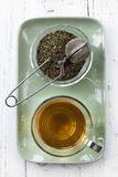 Tea Still Life. Glass of tea, with bowl of loose tea and a tea ball.  Overhead view Royalty Free Stock Photos