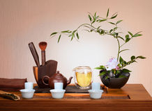 Tea still life. Flowers , kettle, cups, pile of dry tea royalty free stock images