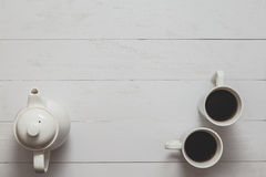 Tea still life with kettle and two cups on white wooden desk. Stock Image