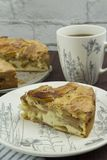 A piece of American apple pie on a white plate with a large white cup of tea. Tea still life. A slice of homemade apple pie with a large cup of tea on a wooden stock photography