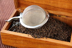 Tea strainer with a black tea Stock Photography