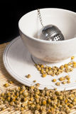 Tea strainer with dry chamomile in white cup Stock Images