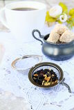 Tea strainer with a fragrant black tea. And cups in the background stock photography