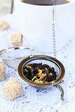 Tea strainer with a fragrant black tea. And cups in the background stock image