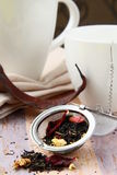 Tea strainer with a fragrant black tea and cups. In the background stock photography