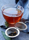 Tea strainer with a fragrant black tea and cups. In the background stock photo