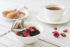 Tea strainer and rose buds Stock Photo