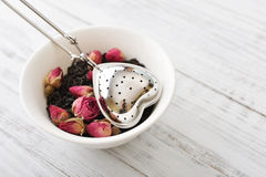 Tea strainer and rose buds Stock Images