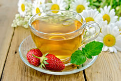 Tea with strawberries and daisies on board Royalty Free Stock Photography