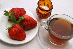 Tea and strawberry. Tea cup with candle and strawberry on dish Stock Photography