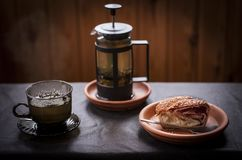 Tea and strudel. A cup of tea, a teapot and a strudel on the table Stock Images